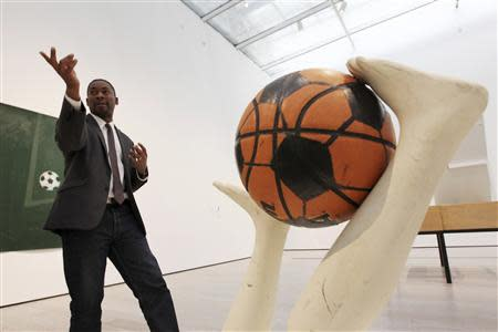 """Curator Sirmans gestures near """"Free Throw"""" by Caroll during construction of the exhibition, """"Futbol: The Beautiful Game"""", at the Los Angeles County Museum of Art in Los Angeles"""