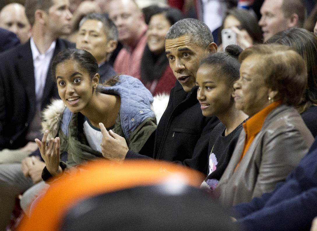 President Barack Obama, second from with first lady Michelle Obama, and their daughters Malia, left, Sasha, second from right, and mother-in-law Marian Robinson, right, arrive at the Comcast Center in College Park, Md., to watch his brother-in-law Oregon State Beavers Coach Craig Robinson's basketball team play against the Maryland Terrapins, Sunday, Nov. 17, 2013. (AP Photo/Manuel Balce Ceneta)