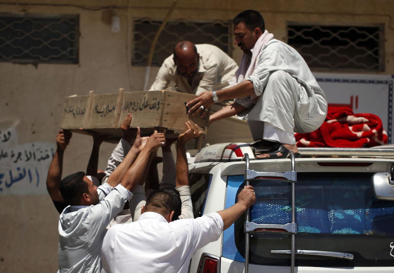 Mourners unload the coffin of an Iraqi man who was killed along with his wife in a car bomb attack during their honeymoon, his family said, during the funeral in the Shiite holy city of Najaf, 100 miles (160 kilometers) south of Baghdad, Iraq, Sunday, Aug. 11, 2013. A wave of car bombings targeting those celebrating the end of Ramadan across Iraq killed scores of people Saturday, a bloody reminder of the inability of Iraqi authorities to stop violence threatening to spiral out of control. (AP Photo/ Haider Hamdani)
