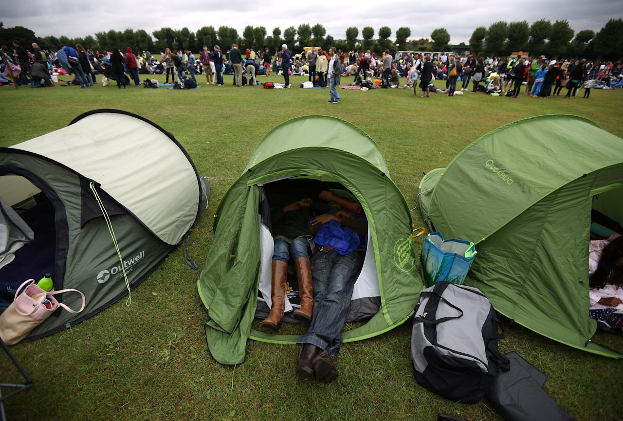LONDON, ENGLAND - JUNE 28: Non-ticket holders shelter in a tent as they wait in a field near the Wimbledon Lawn Tennis Championships on June 28, 2013 in London, England. Rain has delayed play on the outside courts today on day five of the tournament. (Photo by Peter Macdiarmid/Getty Images)