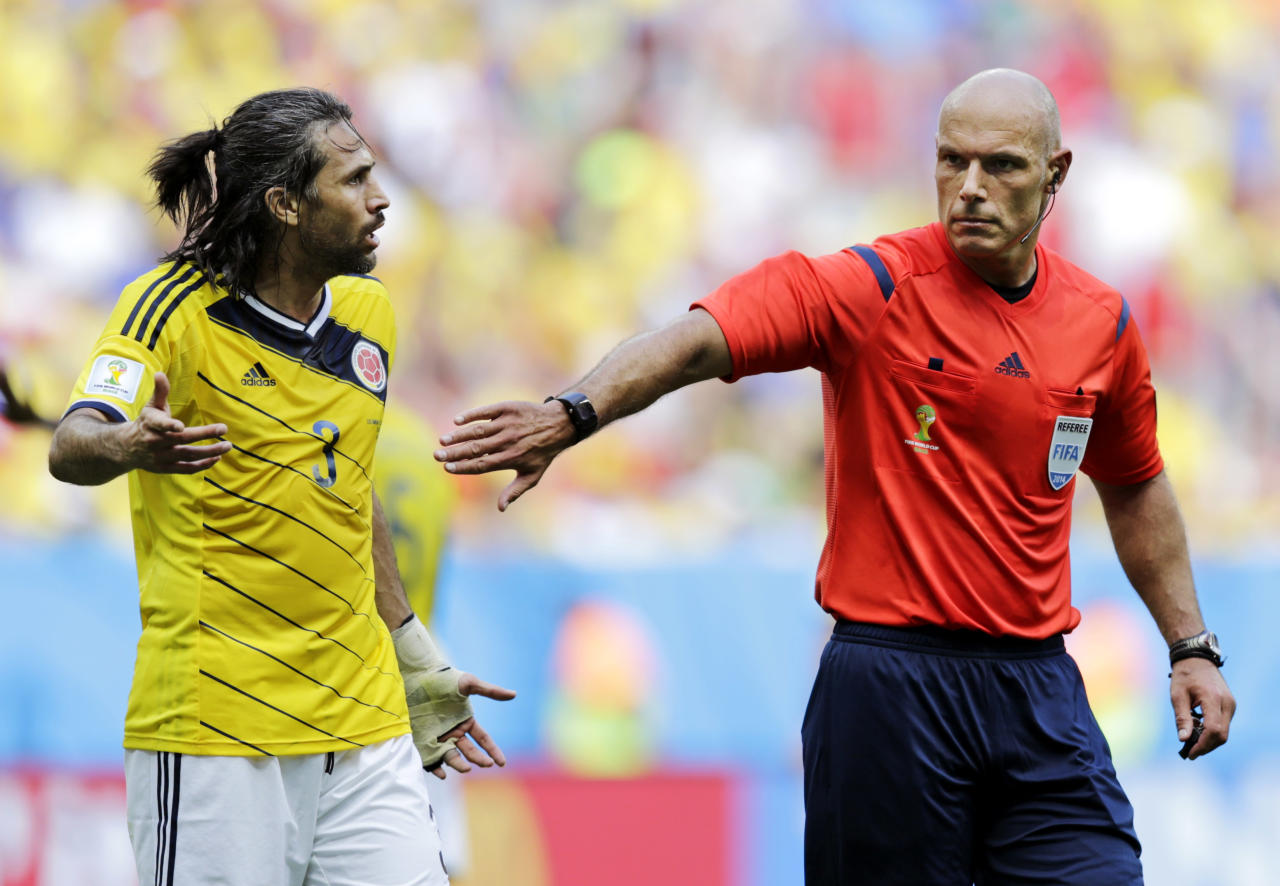 Referee Howard Webb, right, from England holds back Colombia's Mario Yepes during the group C World Cup soccer match between Colombia and Ivory Coast at the Estadio Nacional in Brasilia, Brazil, Thursday, June 19, 2014.  (AP Photo/Fernando Llano)