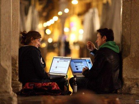 man and woman at laptops computers couple