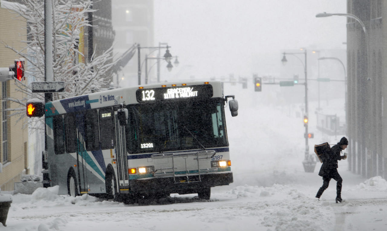 A pedestrian crosses the street in front of a city bus stuck in the snow Tuesday, Feb. 26, 2013 in Kansas City, Mo. The second major snowstorm in a week battered the nation's midsection Tuesday, dropping a half-foot or more of heavy, wet snow across Missouri and Kansas and cutting power to thousands. (AP Photo/The Kansas City Star, Keith Myers)
