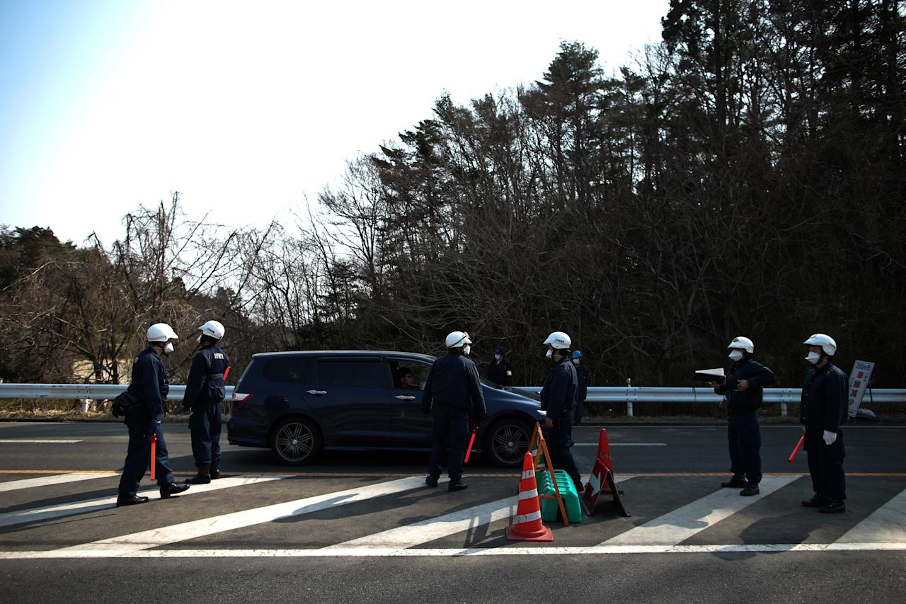 NAMIE, JAPAN - MARCH 10:  Policemen stand at a checkpoint in Namie, Fukushima Prefecture, prior to the second anniversary commemoration of the tsunami and earthquake on March 10, 2013 in Namie, Japan. Japan on March 11 will commemorate the second anniversary of the magnitude 9.0 earthquake and following tsunami, that claimed more than 18,000 lives.  (Photo by Athit Perawongmetha/Getty Images)