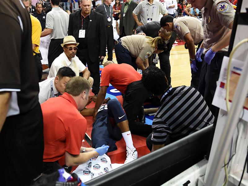 Paul George of the 2014 USA Basketball Men's National Team is tended to as he lies on the court after badly injuring his leg, at the Thomas & Mack Center in Las Vegas, Nevada, on August 1, 2014