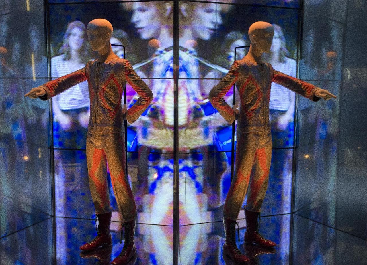 A reflection of the costume that David Bowie wore as Ziggy Stardust on tour and during a performance of 'Starman' on British pop music show Top of The Pops, is photographed as part of a retrospective David Bowie exhibition, entitled David Bowie Is, at the V&A Museum in west London, Wednesday, Mar. 20, 2013, thats features 300 objects including handwritten lyrics, original costumes, fashion, photography, film, music videos, set designs and Bowie's own instruments.(Photo by Joel Ryan/Invision/AP)
