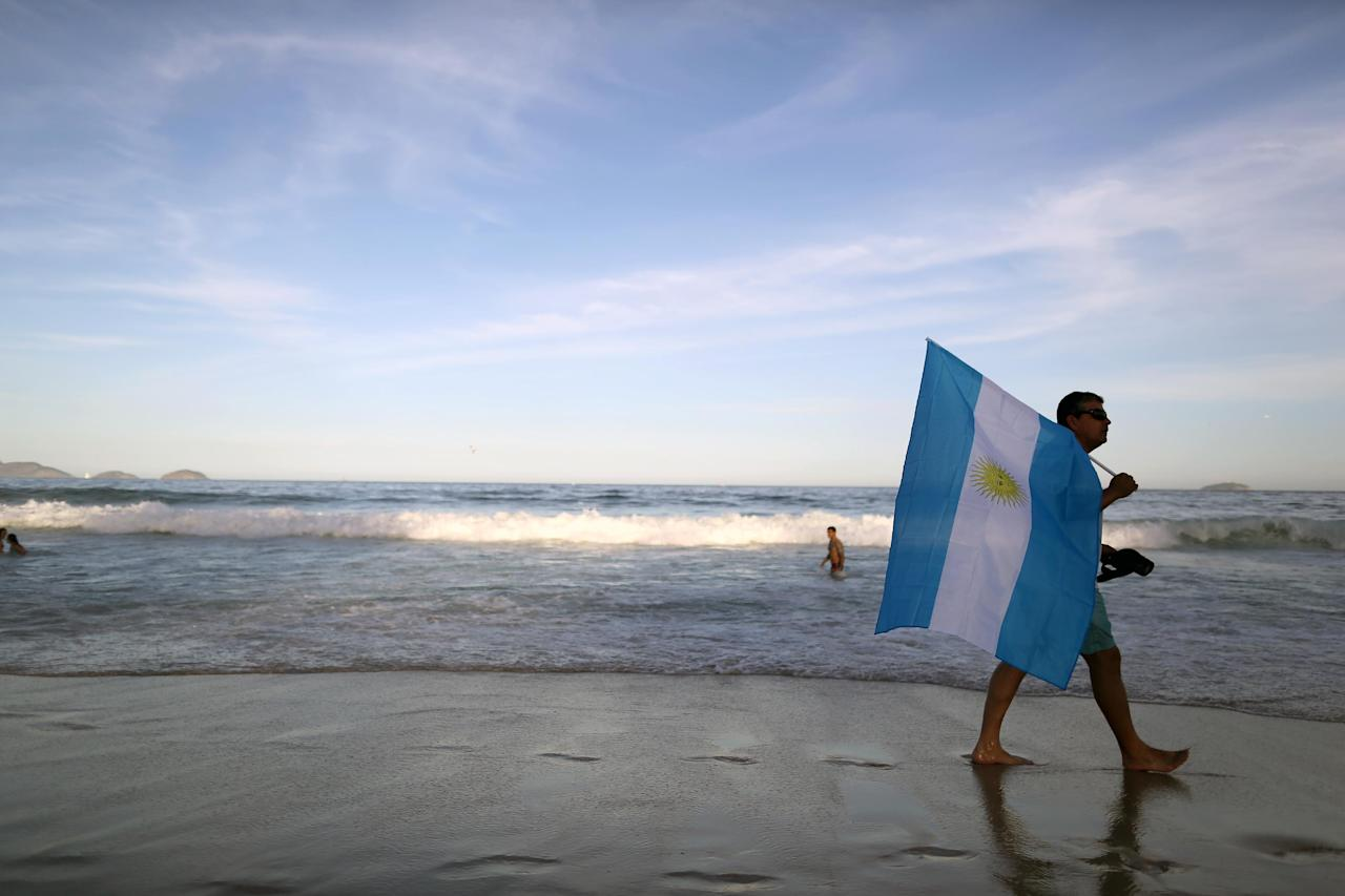 An Argentine fan with an Argentine flag walks along Copacabana beach in Rio de Janeiro, Brazil, Saturday June 14, 2014. Argentine fans, many dressed in their team's traditional blue and white, celebrated on the Copacabana beachfront ahead of Argentina's World Cup match against Bosnia-Herzegovina Sunday in Rio's iconic Maracana stadium. (AP Photo/Leo Correa)