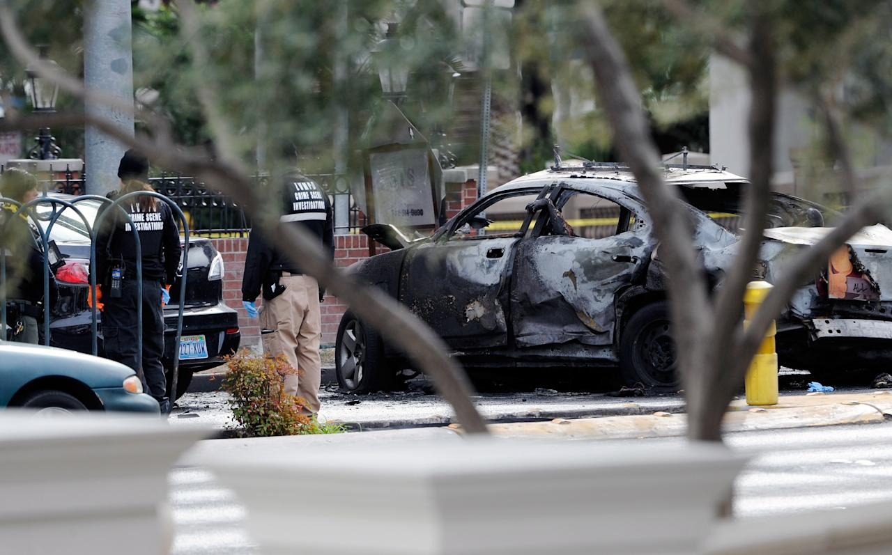 LAS VEGAS, NV - FEBRUARY 21:  (EDITORS NOTE: Image contains graphic content.)  A burned taxi cab sits at the site of what is being described as a gun battle between shooters in two vehicles along the Las Vegas Strip on February 21, 2013 in Las Vegas, Nevada. According to reports gunshots were fired between black SUV at a Maserati, causing the Maserati to crash into a taxi, that burst into flames. Five vehicles were involved in the subsequent crash with the Maserati driver and two people in the taxi being killed.  (Photo by David Becker/Getty Images)