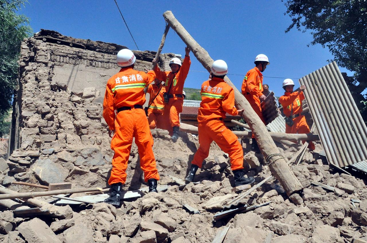 In this photo released by Xinhua News Agency, rescuers clear the debris of a damaged house in quake-hit Majiagou Village of Minxian County, northwest China's Gansu Province, Monday, July 22, 2013. The toll of dead and injured continues to rise after an earthquake struck a dry, hilly farming area in western China early this morning. (AP Photo/Xinhua, Guo Gang) NO SALES
