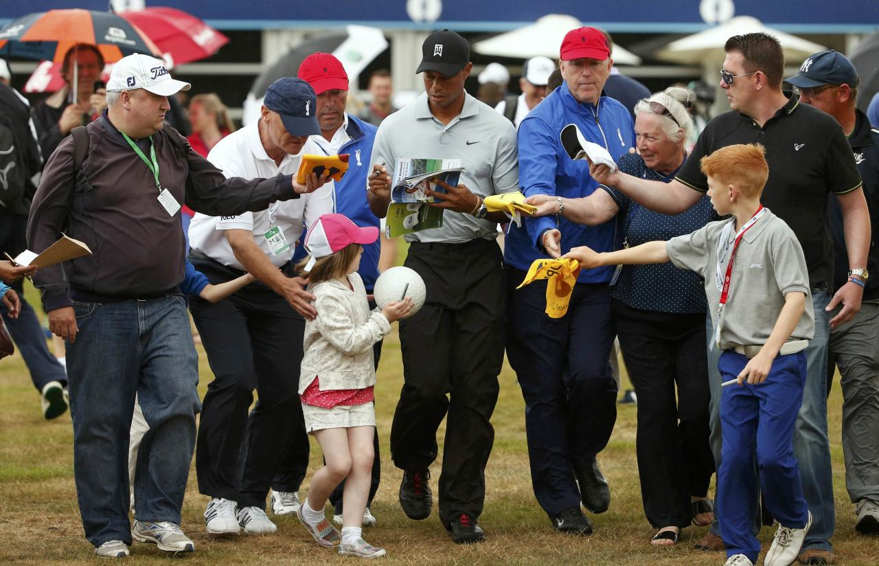 Tiger Woods of the U.S. signs autographs for fans as he walks back to the clubhouse after a practice round ahead of the British Open Championship at the Royal Liverpool Golf Club in Hoylake, northern England July 16, 2014. REUTERS/Cathal McNaughton (BRITAIN - Tags: SPORT GOLF)