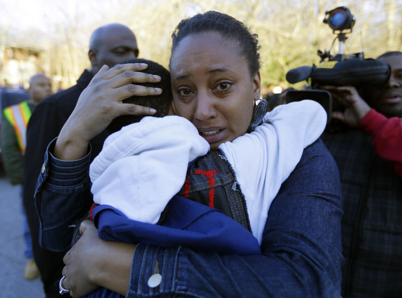 A woman comforts a child after after a shooting at an Price Middle school in Atlanta Thursday, Jan. 31, 2013. A 14-year-old boy was wounded outside the school Thursday afternoon and a fellow student was in custody as a suspect, authorities said. No other students were hurt. (AP Photo/John Bazemore)
