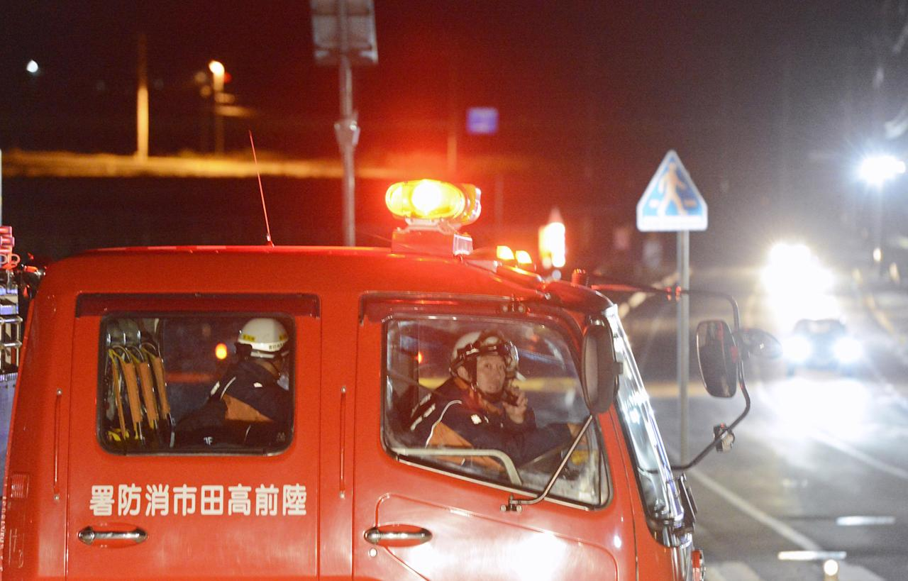 Firefighters in a fire fighting vehicle call for residents to evacuate from coastal areas in Rikuzentakata in Iwate Prefecture, Friday, Dec. 7, 2012 after a tsunami warning has been issued following a strong earthquake struck off the coast of northeastern Japan. It is the same region that was hit by a massive earthquake and tsunami last year. (AP Photo/Kyodo News) JAPAN OUT, MANDATORY CREDIT, NO LICENSING IN CHINA, FRANCE, HONG KONG, JAPAN AND SOUTH KOREA