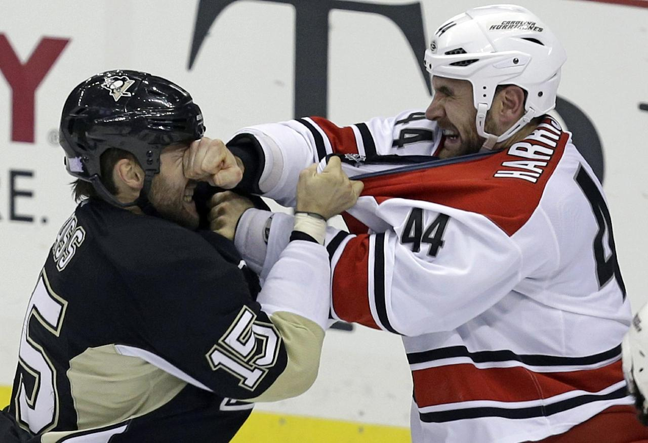 Carolina Hurricanes' Jay Harrison (44) lands a punch in the face of Pittsburgh Penguins' Tanner Glass (15) during a first-period fight in an NHL hockey game in Pittsburgh, Tuesday, Oct. 8, 2013. (AP Photo/Gene J. Puskar)