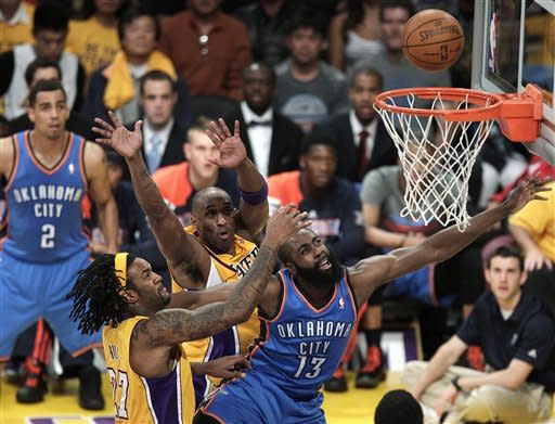 Oklahoma City Thunder's James Harden, right, puts up a shot against Los Angeles Lakers' Kobe Bryant, center, and Jordan Hill during the first half in Game 3 of an NBA basketball playoffs Western Conference semifinal in Los Angeles, Friday, May 18, 2012. (AP Photo/Jae C. Hong)