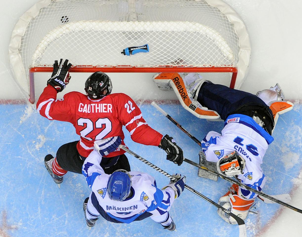 Canada's forward Frederik Gauthier (L) scores past Finland's goalie Juuse Saros during a semi-final game of the IIHF U18 International Ice Hockey World Championship in Sochi on April 26, 2013. Canada von 3-1.  AFP PHOTO / ALEXANDER NEMENOVALEXANDER NEMENOV/AFP/Getty Images