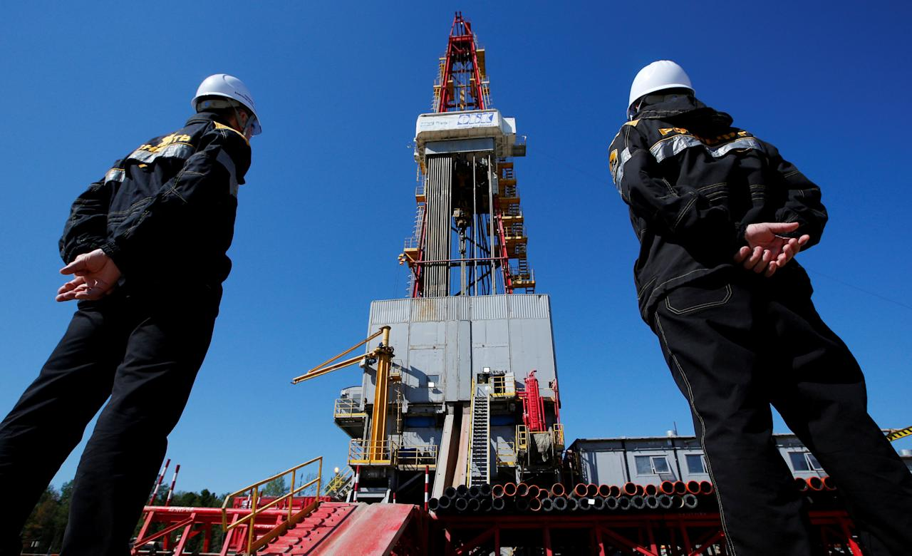Workers look at a drilling rig at a well pad of the Rosneft-owned Prirazlomnoye oil field outside the West Siberian city of Nefteyugansk, Russia, August 4, 2016. REUTERS/Sergei Karpukhin/File Photo     TPX IMAGES OF THE DAY