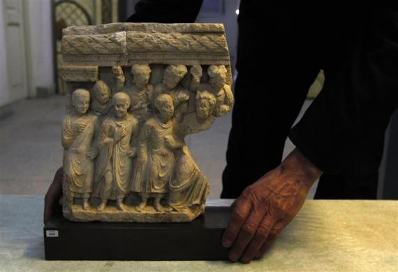An Afghan specialist displays an ancient pre-Islamic sculpture that was returned to Afghanistan at the Afghan National Museum in Kabul January 30, 2012. Germany returned the sculpture looted during Afghanistan's civil war, giving hope to Kabul's cultural mavens that the rest of its stolen treasures will also make their way home.