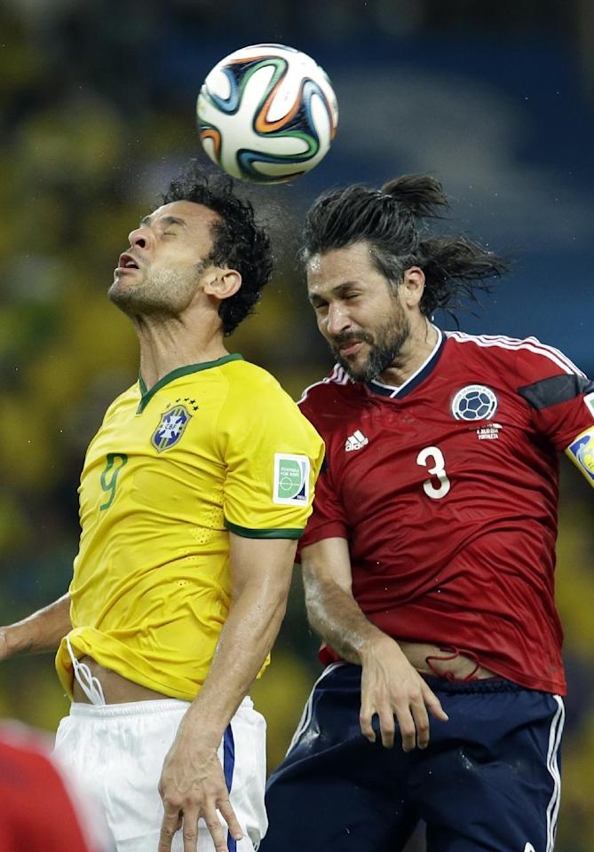Brazil's Fred and Colombia's Mario Yepes go for a header during the World Cup quarterfinal soccer match between Brazil and Colombia at the Arena Castelao in Fortaleza, Brazil, Friday, July 4, 2014. (AP Photo/Hassan Ammar)