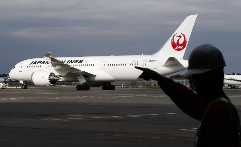A staff of JAL walks past one of the company's Boeing Co's 787 Dreamliner plane at Narita international airport in Narita, east of Tokyo