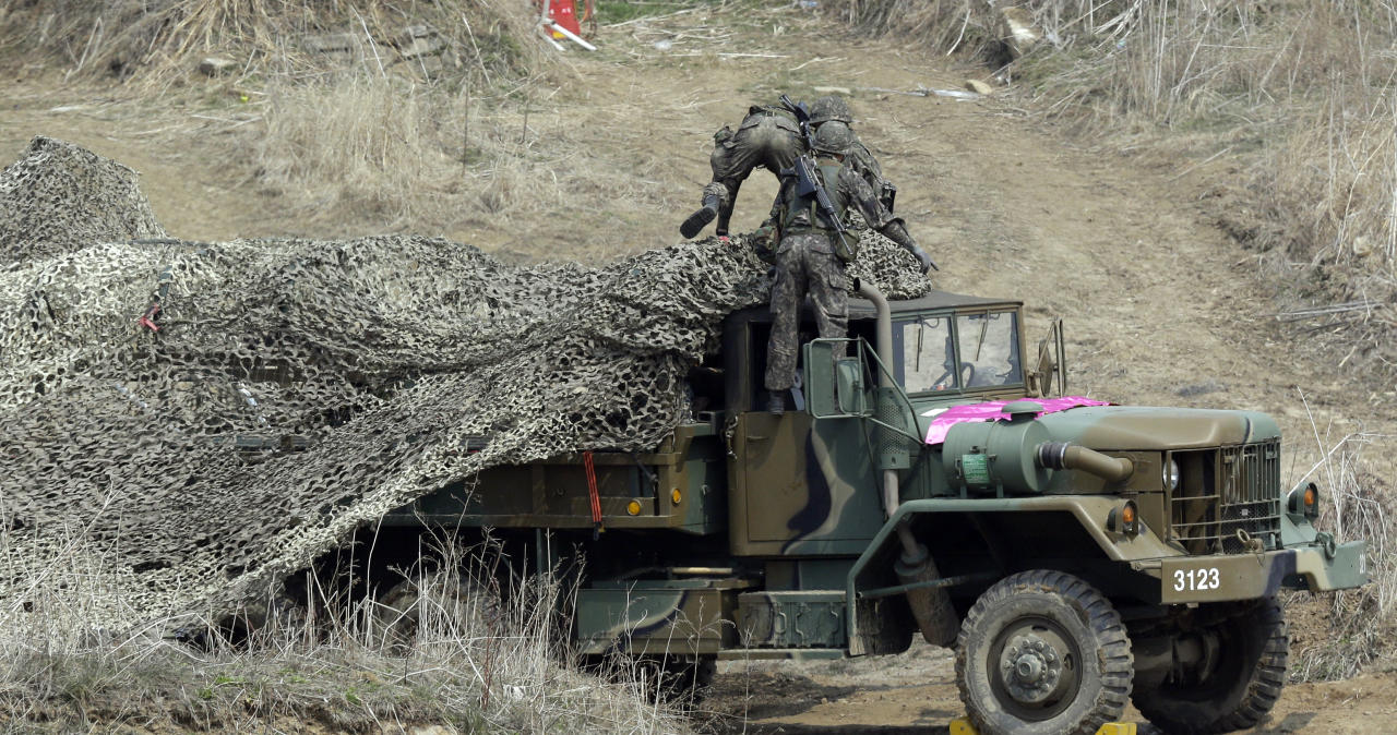 "South Korean soldiers place a camouflage net over their military vehicle during a military exercise near the border village of Panmunjom in Paju, north of Seoul, South Korea, Thursday, April 4, 2013. North Korea warned Thursday that its military has been cleared to attack the U.S. using ""smaller, lighter and diversified"" nuclear weapons, while the U.S. said it will strengthen regional protection by deploying a missile defense system to Guam. (AP Photo/Lee Jin-man)"
