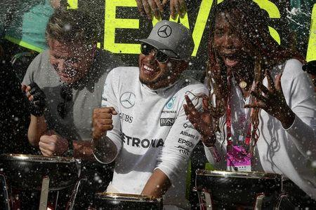 Formula One F1 - U.S. Grand Prix - Circuit of the Americas, Austin, Texas, U.S., 23/10/16. Tennis star Venus Williams (R), chef Gordon Ramsay (L) and race-winning Mercedes driver Lewis Hamilton of Britain are sprayed with champagne by crew members after Hamilton came back  to celebrate with his team and visitors after the race.    REUTERS/Adrees Latif