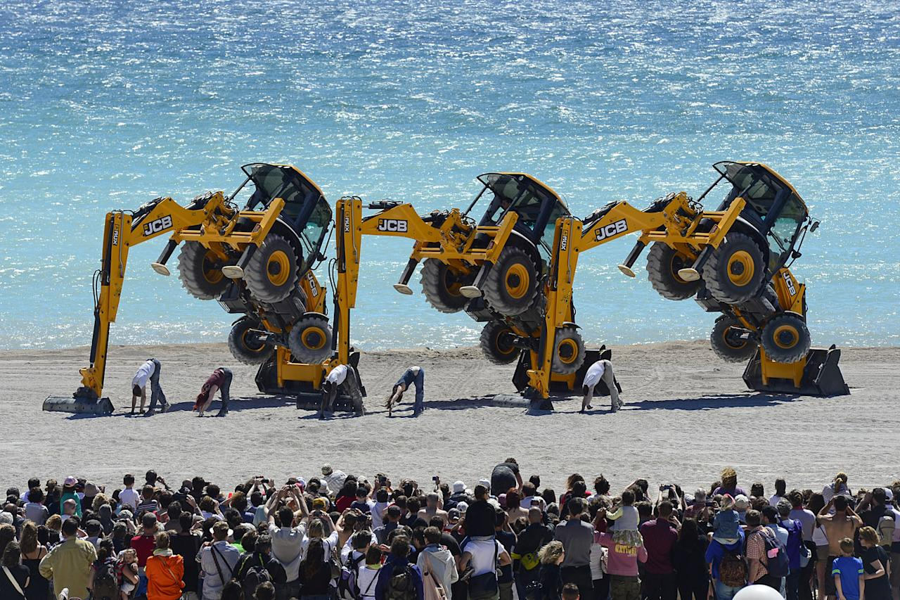 "Dancers from the British dance theatre company ""Motionhouse"" perform a ""Traction"" show with excavators on May 10, 2013, on the Prado beach in Marseille, southern France, for a free spectacle in front of thousands of people, as part of the ""Marseille-Provence European Capital of Culture 2013"" program. AFP PHOTO / BORIS HORVAT"