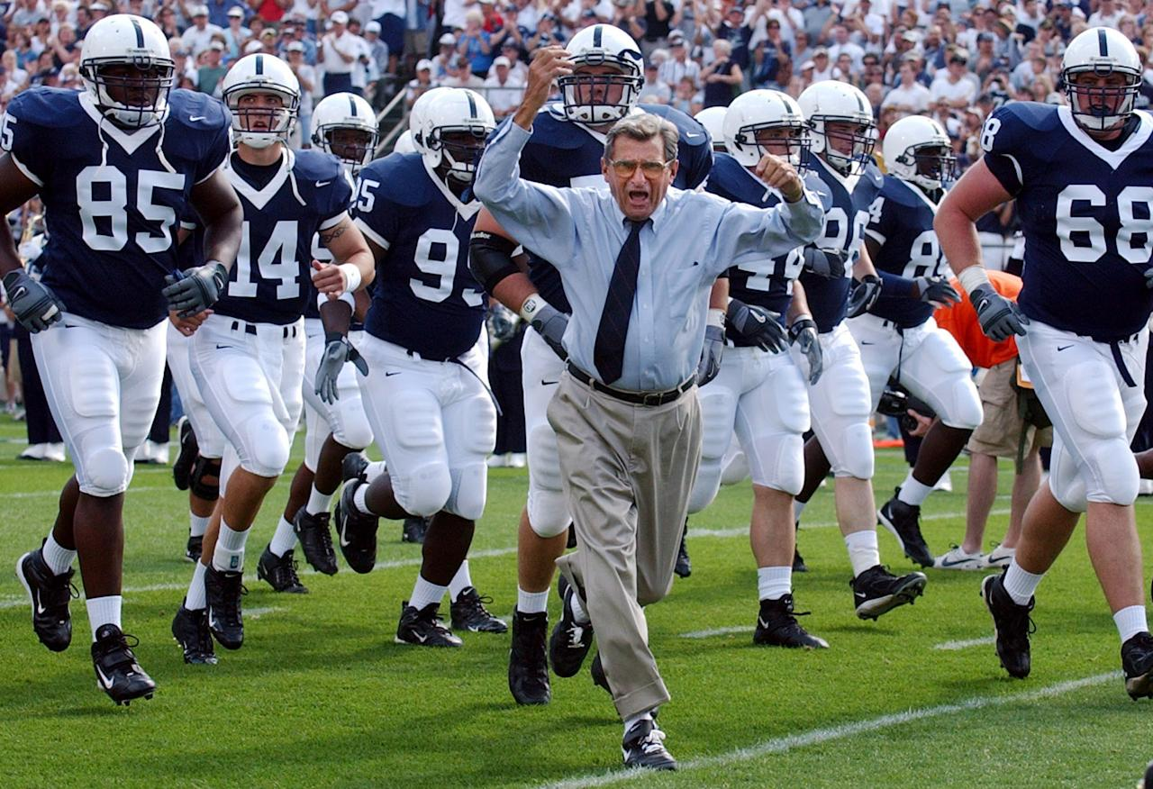 FILE - In this Sept. 4, 2004 file photo, Penn State football coach Joe Paterno leads his team onto the field before a game against Akron, in State College, Pa. Paterno say he plans to retire at the end of the season, his long and illustrious career brought down because he failed to do all he could about an allegation of child sex abuse against a former assistant. (AP Photo /Carolyn Kaster, File)