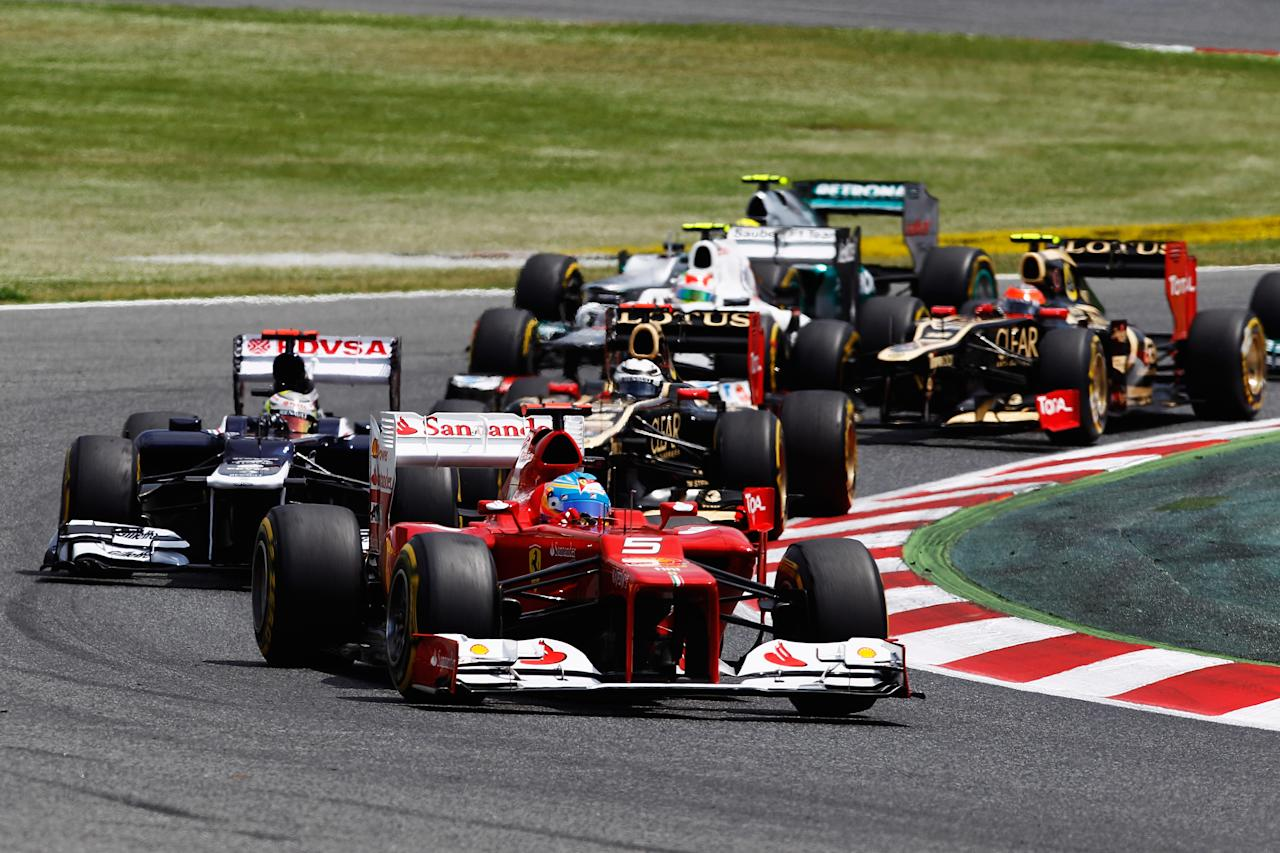 BARCELONA, SPAIN - MAY 13:  Fernando Alonso of Spain and Ferrari takes the lead from Pastor Maldonado of Venezuela and Williams at the start of the Spanish Formula One Grand Prix at the Circuit de Catalunya on May 13, 2012 in Barcelona, Spain.  (Photo by Paul Gilham/Getty Images)
