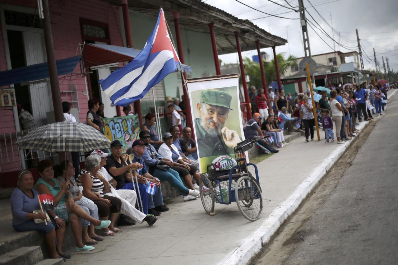 People hold Cuban flags and images of Fidel Castro as they await the arrival of the caravan carrying the late Cuban President's ashes in Jatibonico, Cuba, December 1, 2016.   REUTERS/Edgard Garrido  TPX IMAGES OF THE DAY