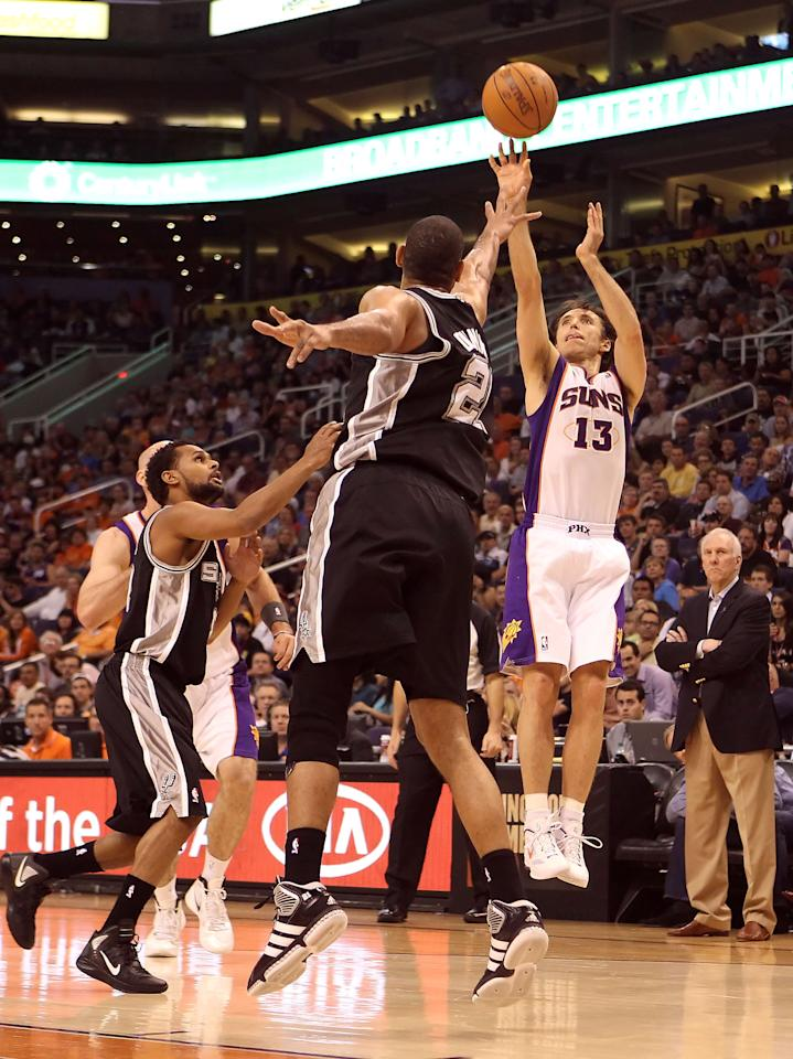 PHOENIX, AZ - MARCH 27:  Steve Nash #13 of the Phoenix Suns puts up a shot over Tim Duncan #21 of the San Antonio Spurs during the NBA game at US Airways Center on March 27, 2012 in Phoenix, Arizona. The Spurs defeated the Suns 107-100. NOTE TO USER: User expressly acknowledges and agrees that, by downloading and or using this photograph, User is consenting to the terms and conditions of the Getty Images License Agreement.  (Photo by Christian Petersen/Getty Images)