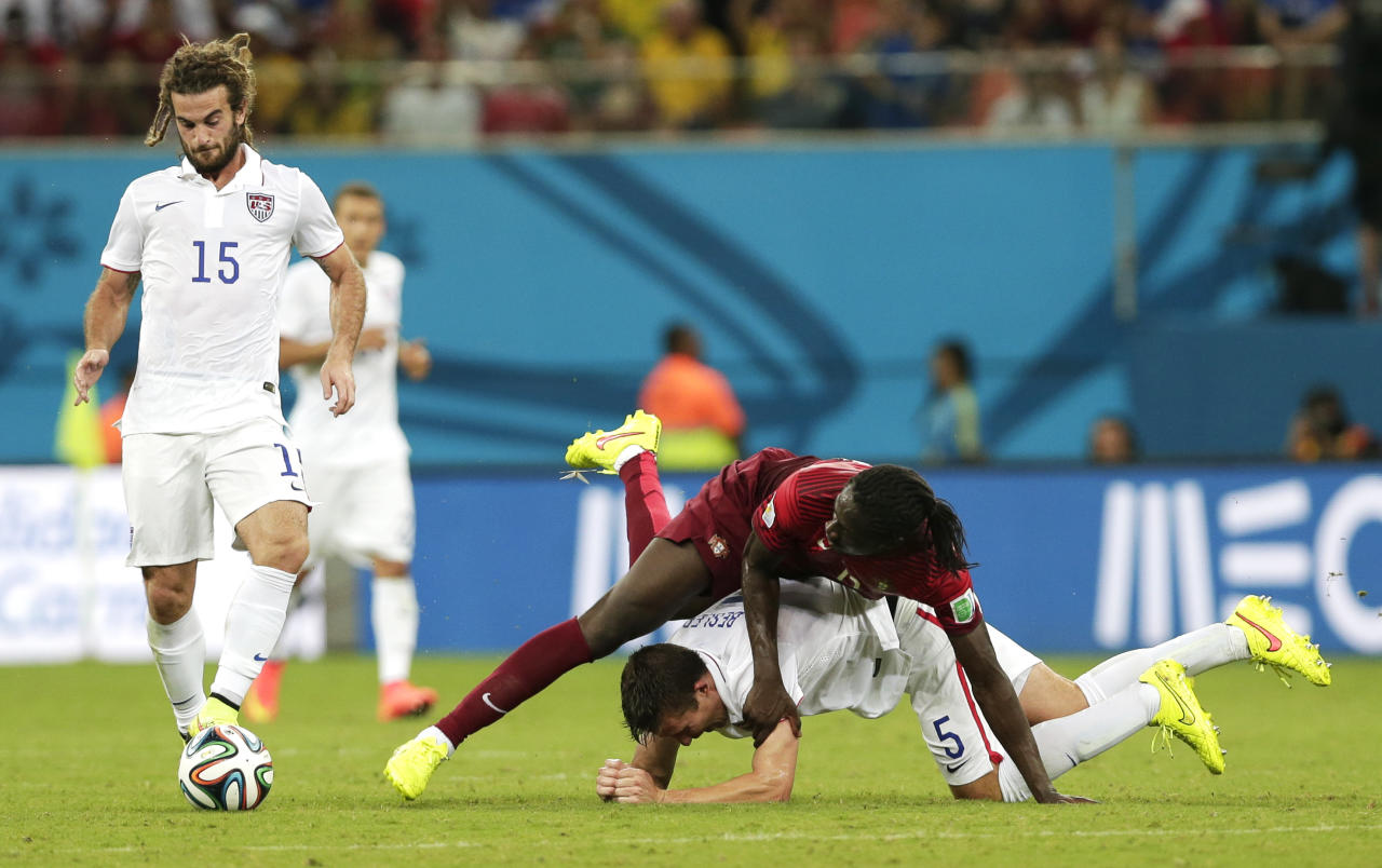 United States' Kyle Beckerman, left, controls the ball as Portugal's Eder lands on top of United States' Matt Besler during the group G World Cup soccer match between the United States and Portugal at the Arena da Amazonia in Manaus, Brazil, Sunday, June 22, 2014. (AP Photo/Marcio Jose Sanchez)