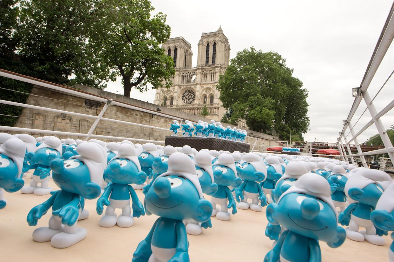 PARIS, FRANCE - JUNE 22: 3000 smurf figurines pass Notre Dame as they travel down the River Seine to mark Global Smurfs Day on June 22, 2013 in Paris, France. (Photo by Dominique Charriau/Getty Images for Sony Pictures Entertainment)