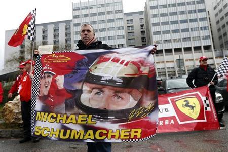 Philippe, a fan from Lyon, waves a flag as he attends a silent 45th birthday tribute to seven-times former Formula One world champion Michael Schumacher in front of the CHU hospital emergency unit in Grenoble, French Alps, where Schumacher is hospitalized