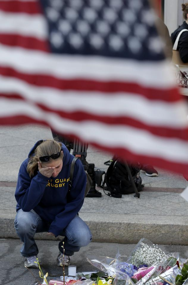 Jillian Blenis, 30, of Boston, reacts while stopping at a makeshift memorial, Wednesday, April 17, 2013, in Boston. The city continues to cope following Monday's explosions near the finish line of the Boston Marathon. (AP Photo/Julio Cortez)