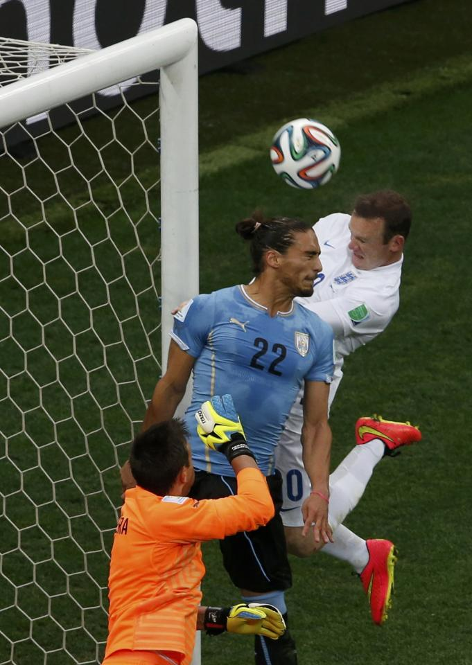 England's Wayne Rooney (R) heads the ball towards the goal, which hits the crossbar instead, beside Uruguay's Martin Caceres (C) and Fernando Muslera during their 2014 World Cup Group D soccer match at the Corinthians arena in Sao Paulo June 19, 2014. REUTERS/Paulo Whitaker (BRAZIL - Tags: SOCCER SPORT WORLD CUP TPX IMAGES OF THE DAY)