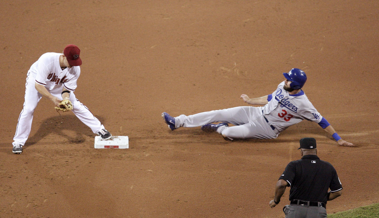 The Los Angeles Dodgers' Scott Van Slyke, top right, is forced out at second by the Diamondbacks' Aaron Hill, left, as umpire Laz Diaz watches the play during the Major League Baseball opening game between the Los Angeles Dodgers and Arizona Diamondbacks at the Sydney Cricket ground in Sydney, Saturday, March 22, 2014. The Dodgers won the game 3-1. (AP Photo/Rick Rycroft)