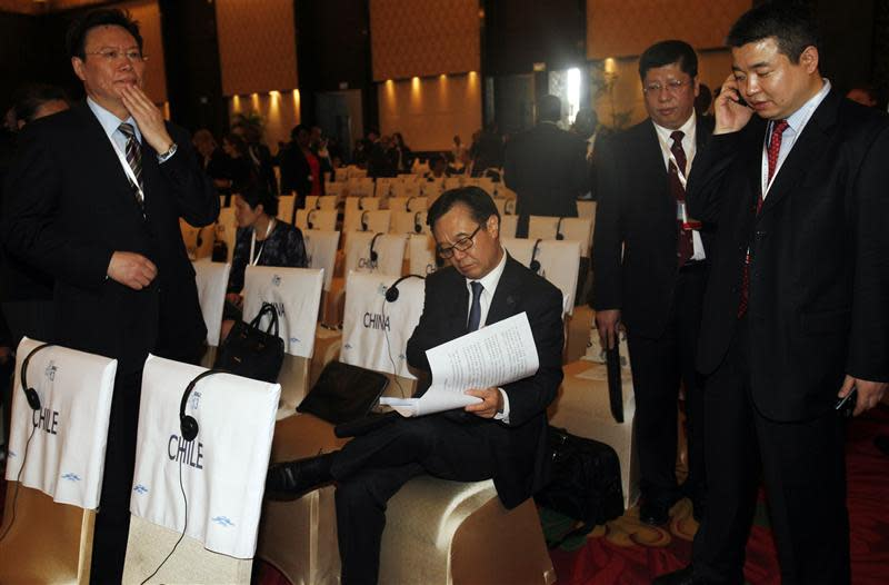 China's chief trade representative Gao Hucheng looks through a document as he attends the ninth WTO Ministerial Conference opening ceremony in Nusa Dua