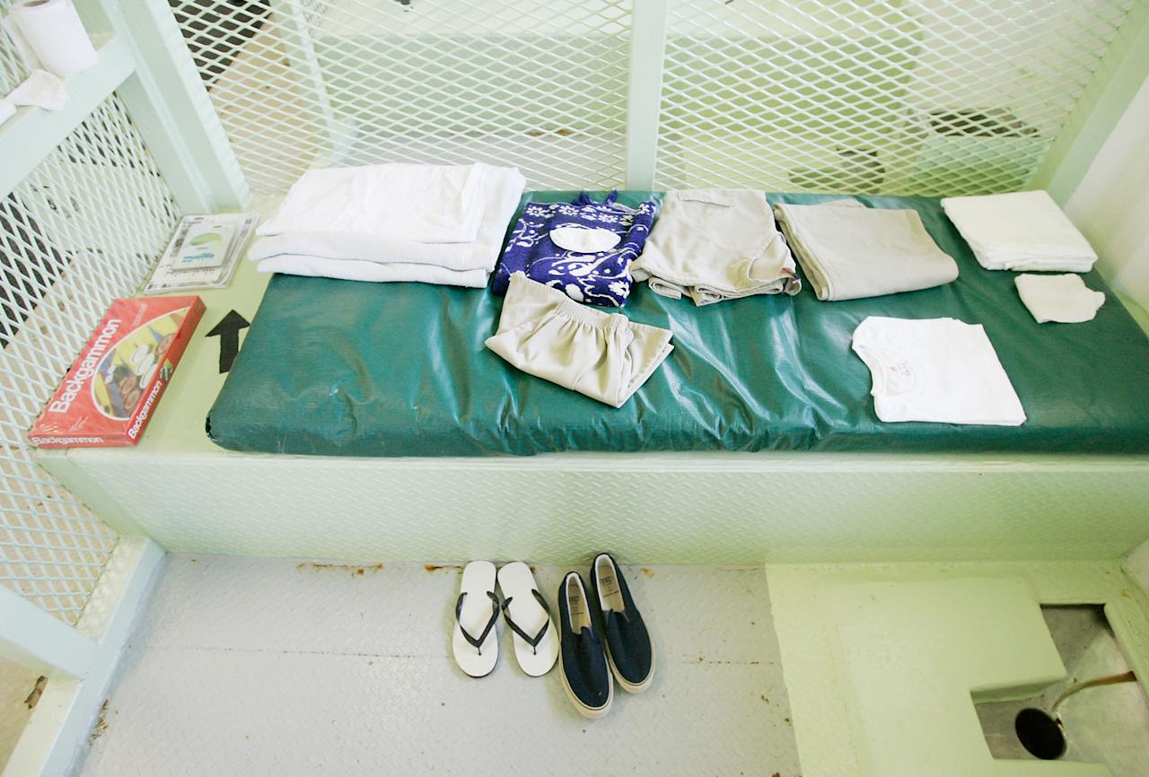 GUANTANAMO BAY, CUBA - MAY 09:  (IMAGE REVIEWED BY U.S. MILITARY PRIOR TO TRANSMISSION)  Clothes and slippers and board games that are given to detainee's sit in a cell of the Camp 2 cell block at Camp Delta May 9, 2006 in Guantanamo Bay, Cuba. Camp Delta was first occupied on April 28, 2002, when 300 detainees previously held at Camp X-Ray were transferred to Camp Delta. The rest of the detainees were moved on April 29. Camp X-Ray closed down on that same day.  (Photo by Mark Wilson/Getty Images)