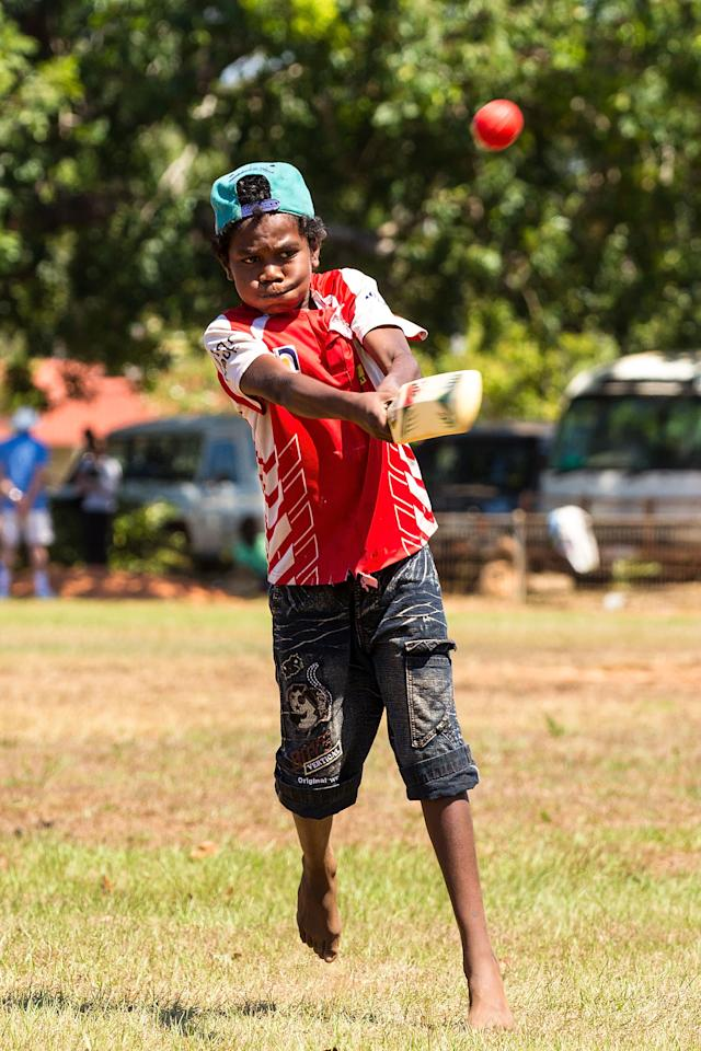 DARWIN, AUSTRALIA - AUGUST 10:  A child plays cricket during a visit by the Australian cricket team to Pirlangimpi of the Tiwi Islands on August 10, 2012 on the Tiwi Islands, Australia.  (Photo by Mark Nolan/Getty Images)