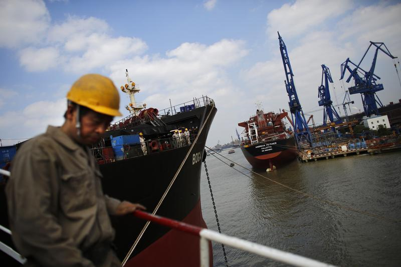 Labourer walks near a ship which is under construction at the Hudong-Zhonghua Shipbuilding company's shipyard in Shanghai