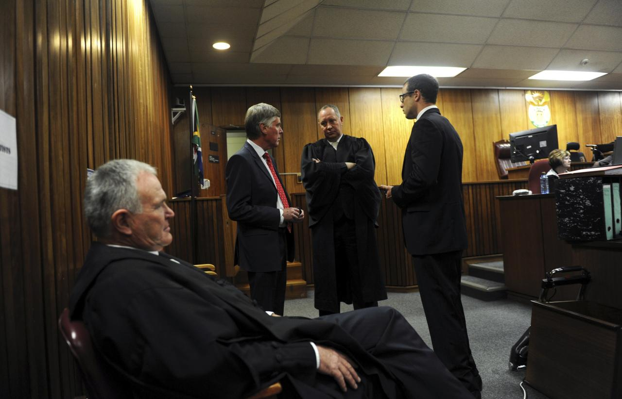 South African Olympic and Paralympic sprinter Oscar Pistorius (R) is seen with his defence team Barry Roux (foreground), Brian Webber (L) and Kenny Oldwage (C) before the closing arguments in the North Gauteng High Court in Pretoria, August 7, 2014. Pistorius is on trial for murdering his girlfriend Reeva Steenkamp at his suburban Pretoria home on Valentine's Day last year. REUTERS/Werner Beukes/Pool (SOUTH AFRICA - Tags: SPORT CRIME LAW ATHLETICS)