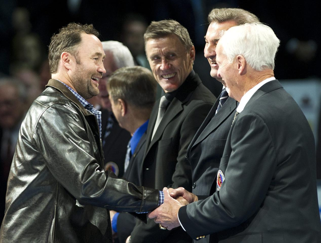 Hall of Fame inductee Ed Belfour, left, shakes hands with Gordie Howe, right, as he takes part in a ceremony before an NHL hockey game between the Toronto Maple Leafs and the Ottawa Senators, Saturday, Nov. 12, 2011, in Toronto. (AP Photo/The Canadian Press, Nathan Denette)