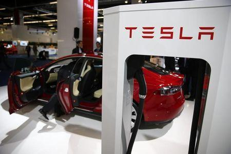 A Tesla model S car with an electric vehicle charging station is displayed at Frankfurt Motor Show