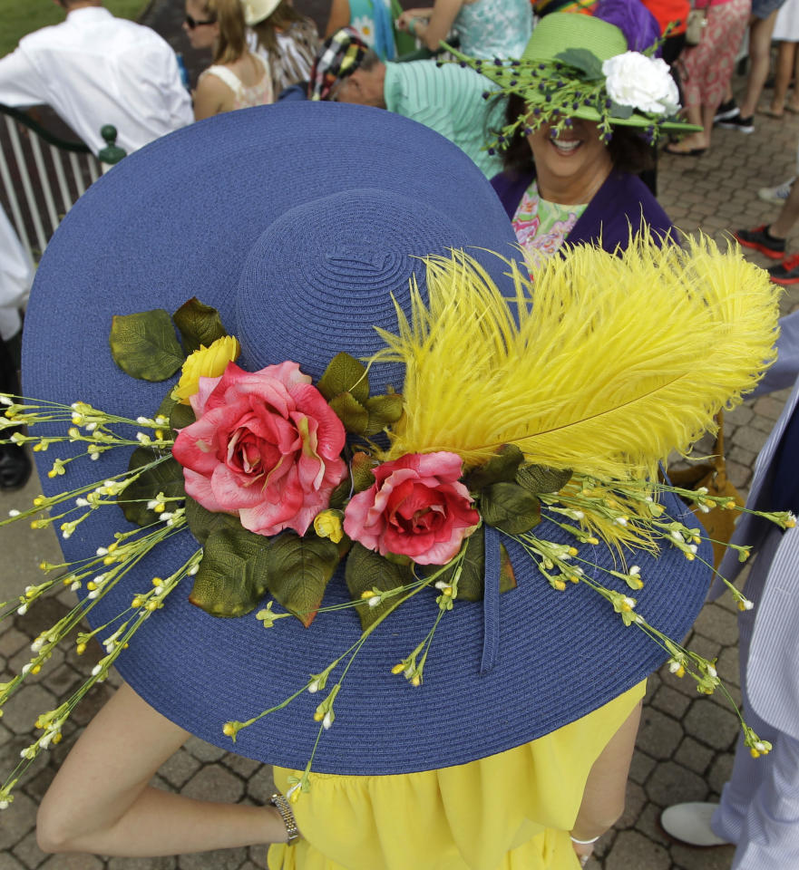 Kimberly Scott, left, from Albany, Ga., chats with a friend in the paddocks before the 138th Kentucky Derby horse race at Churchill Downs, Saturday, May 5, 2012, in Louisville, Ky. The Run for the Roses draws them to Churchill Downs. But what race goers wear is as much a spectacle in itself. (AP Photo/Michael Conroy)