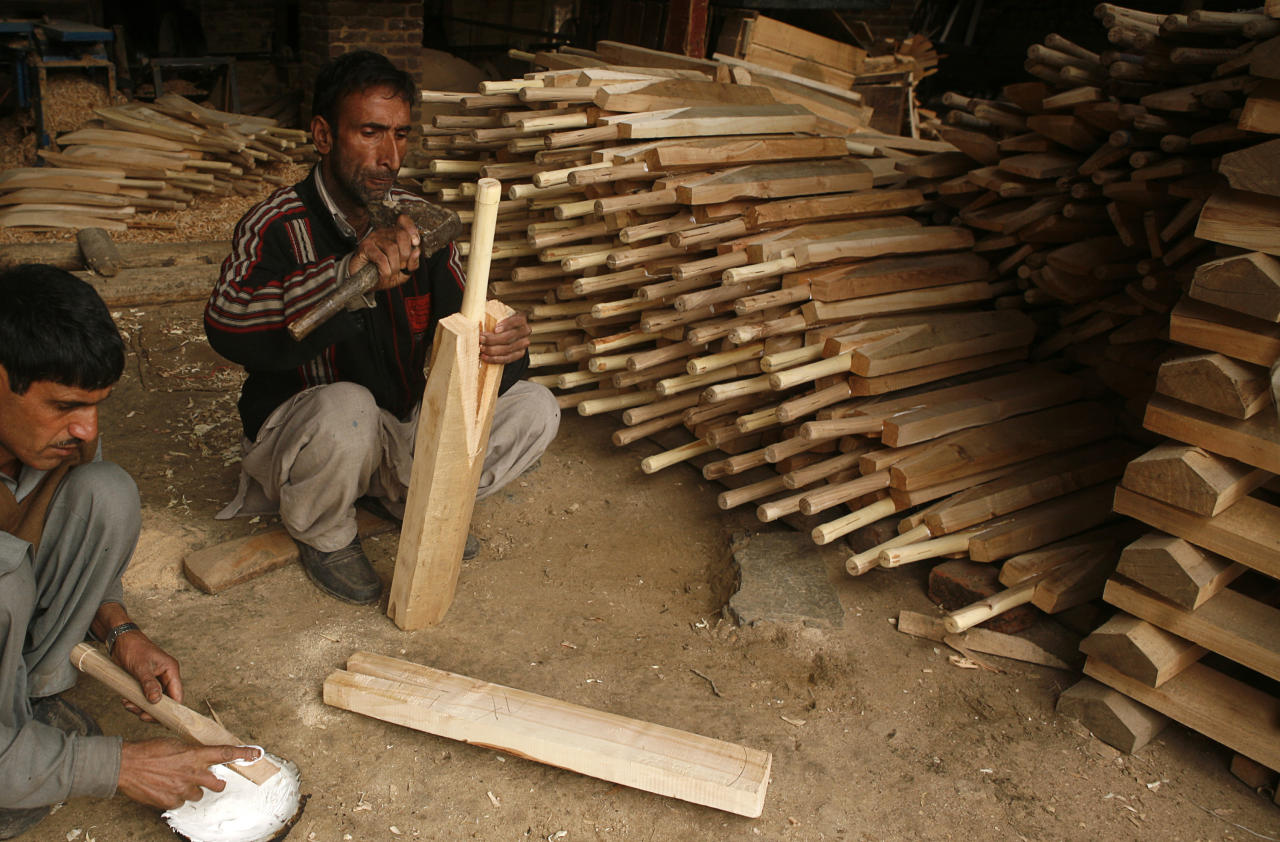 HAlMULLAH, KASHMIR, INDIA - FEBRUARY 16: Workers build cricket bats on February 16, 2011 in Halmullah, near Srinagar, in Kashmir, India.  Cricket bat manufacturers in India are experiencing a boom with the Cricket World Cup beginning in South Asia on February 19. Kashmir willow, whilst less valuable than English willow is widely used in cricket bats found across the globe, and manufacturers in Kashmir are hoping to increase exports on the back of the World Cup interest. Cricket bats in Kashmir made from local willow can be bought for as little as US$11, whereas its English counterpart can command prices of at least US$170. (Photo by Yawar Nazir/Getty Images)