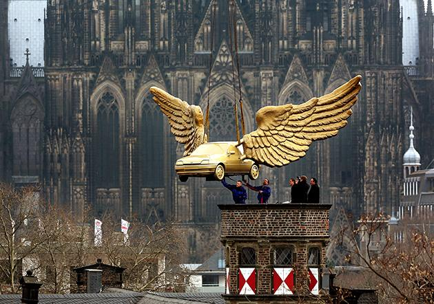 Workers install a golden winged car on the roof of the City Museum in Cologne, western Germany, on April 4, 2013. The car, a creation by German artist HA Schult, is brought back to the roof after its restauration at Ford.  AFP PHOTO / OLIVER BERG