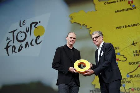 ASO's Laurent Lachaux (R), Commercial and Marketing Director at Amaury Sport Organisation, presents rider Chris Froome of Britain with a gift after the presentation of the itinerary of the 2017 Tour de France cycling race during a news conference in Paris, France, October 18, 2016. REUTERS/Benoit Tessier