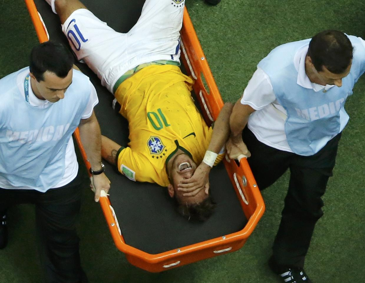 Brazil's Neymar grimaces as he is carried off the pitch after being injured during their 2014 World Cup quarter-finals against Colombia at the Castelao arena in Fortaleza July 4, 2014. REUTERS/Fabrizio Bensch (BRAZIL - Tags: SOCCER SPORT WORLD CUP TPX IMAGES OF THE DAY) TOPCUP