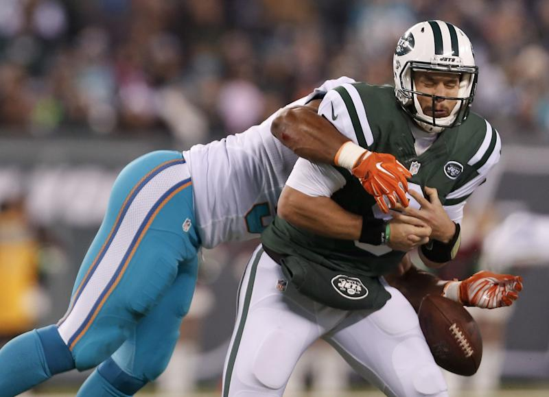 Miami Dolphins pass rusher Cameron Wake, left, crushes New York Jets QB Bryce Petty on Saturday. (AP)