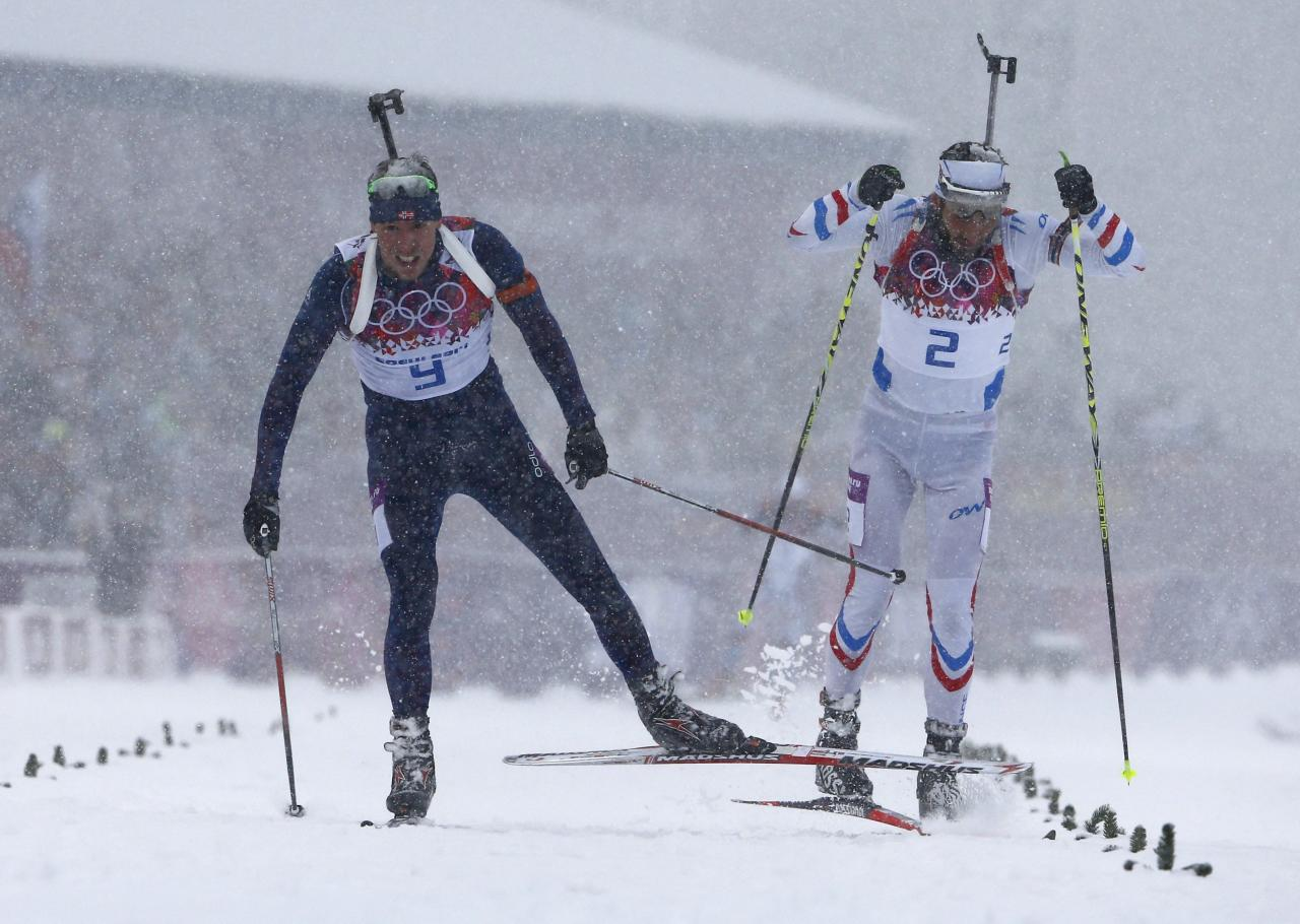 France's Martin Fourcade and Norway's Emil Hegle Svendsen (L) race to the finish line during the men's biathlon 15 km mass start event at the 2014 Sochi Winter Olympics February 18, 2014. Svendsen finished first ahead of Fourcade and Czech Republic's Ondrej Moravec. REUTERS/Carlos Barria (RUSSIA - Tags: OLYMPICS SPORT BIATHLON)